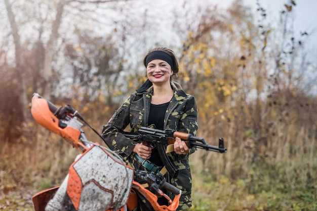 Woman soldier with rifle sitting on motorcycle
