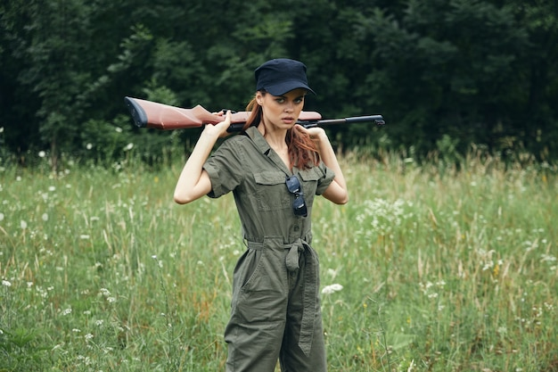 Woman soldier with a weapon in his hands a green jumpsuit and a black cap weapons forest background