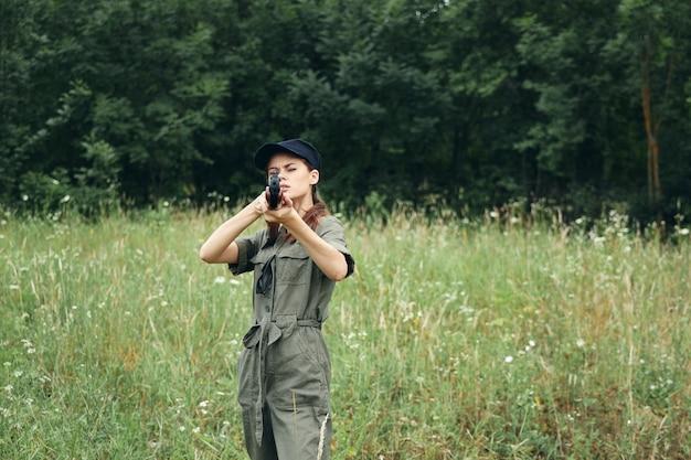 Женщина-солдат женщина держит оружие перед охотой на свежем воздухе с зелеными листьями