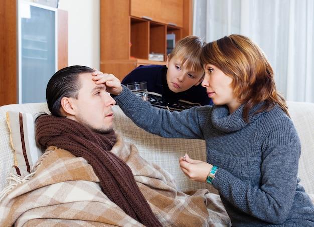 Donna e figlio che si prendono cura dell'uomo malato