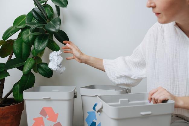 Женщина сортирует мусор, бросает мятую бумагу в маленькую мусорную корзину дома. их несколько, со стрелками разного цвета.