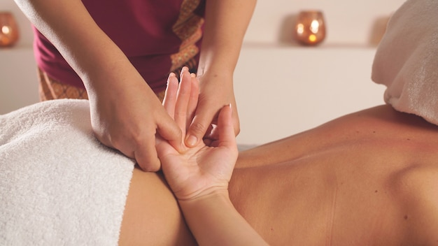 Woman in the spa center gets relaxation from a chinese hand massage