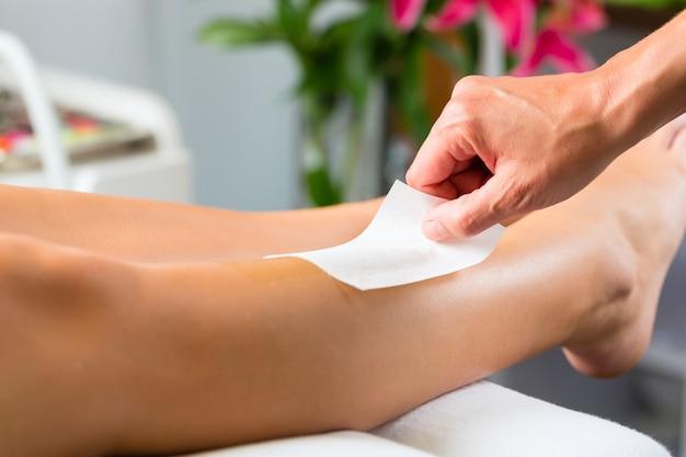 Woman in spa getting leg waxed