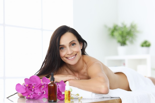 Woman in spa lies on massage table and smiles.