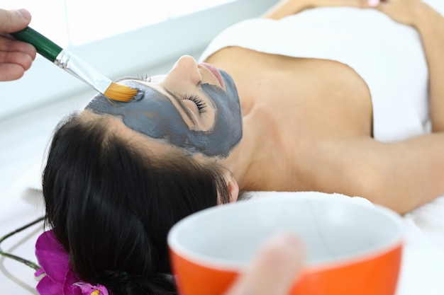 For woman in spa salon, apply clay mask to her face.