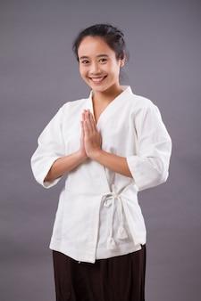 Женщина спа-терапевт приветствует, приветствуя в тайском стиле