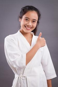 Терапевт спа женщины указывая большой палец вверх. азиатская женщина спа-терапевт