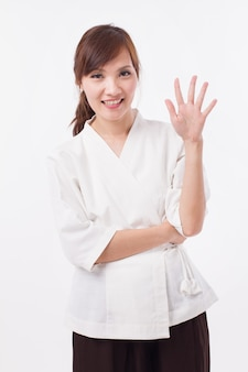 Woman spa therapist pointing up 5 fingers, counting, numbering
