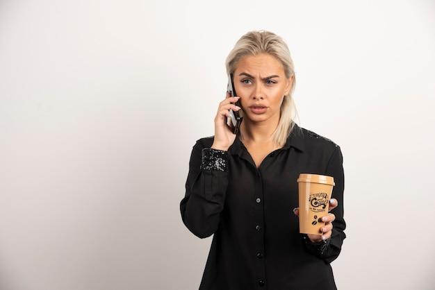 携帯電話で話し、コーヒーを持っている女性。高品質の写真