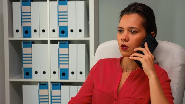 Женщина разговаривает по телефону во время работы в современном офисе. испаноязычный предприниматель, работающий на профессиональном рабочем месте в личной корпоративной компании, разговаривает на смартфоне, глядя на рабочий стол компьютера.