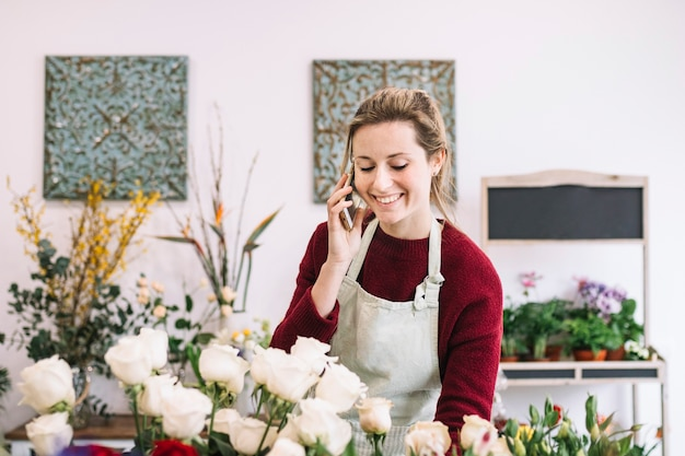 Женщина, говорить на смартфоне в цветочный магазин