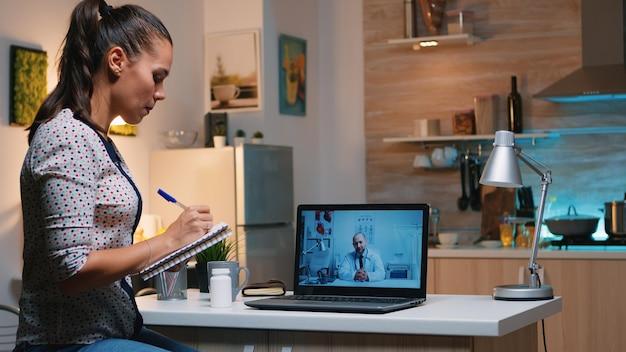 Donna che parla online con il medico che prende appunti durante la telemedicina seduta nella cucina di casa. signora malata che discute durante la consultazione virtuale sui sintomi tenendo il taccuino e scrivendo il trattamento