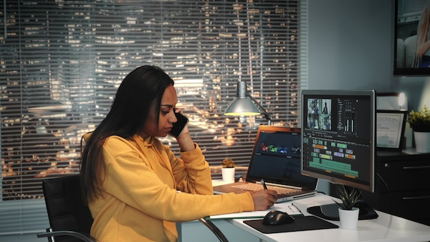 Woman speaking on the phone and writing notes in modern production studio
