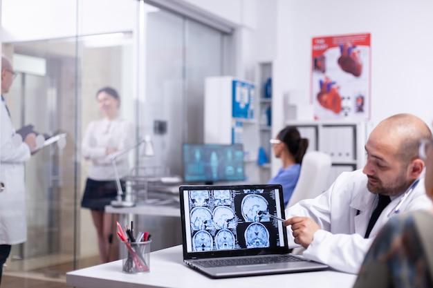 病院でノートパソコンを使用して脳のx線について相談中に医師と話している女性。健康上の苦情を告げる先輩患者訪問医、治療を説明する開業医。