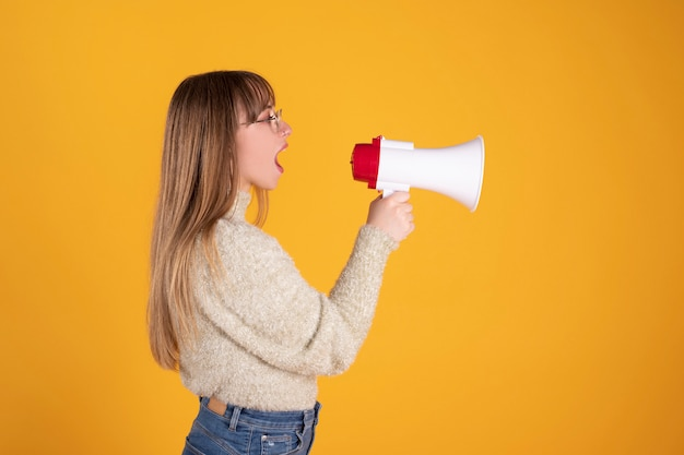 Woman speaks by megaphone yellow background