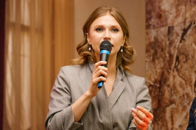 A woman speaks into a microphone, gives a lecture about business. conference training seminar business presentation audience meeting.