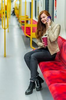 Женщина говорит по мобильному телефону в пустом поезде