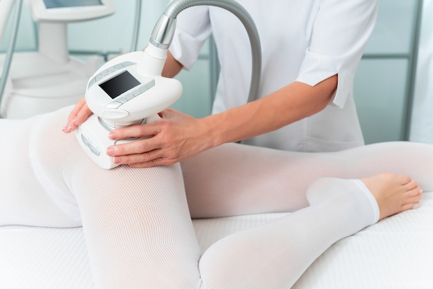 Woman in special white suit getting anti cellulite massage for legs in a spa salon. lpg, and body contouring treatment in clinic.