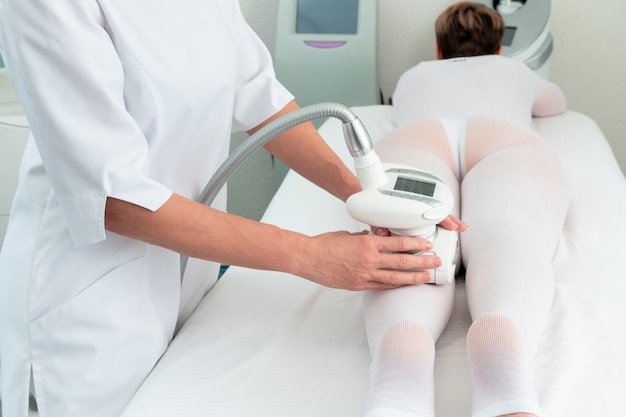 Woman in special white suit getting anti cellulite massage in a spa salon. lpg, and body contouring treatment in clinic.