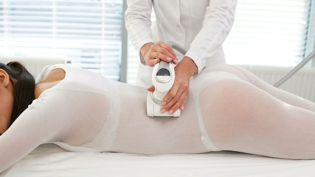 Woman in a special white suit receives a hardware anti-cellulite lpg massage