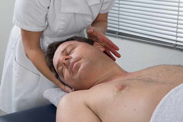 Woman spirit healer doing reiki treatment to a man