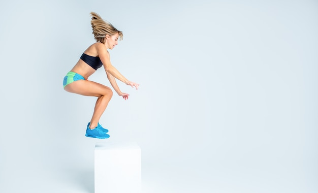 Woman in sport bra and shorts jumpimg on a white cube on a white studio backgroung. copy space. fitnes and training concept