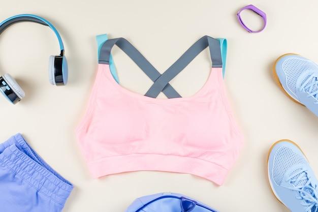 Женская спортивная одежда, кроссовки, наушники и фитнес-трекер на нейтрали