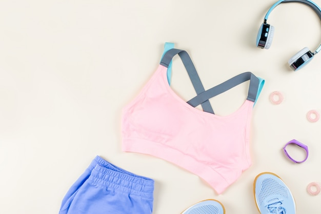Woman sport clothes, sneakers, headphones and fitness tracker on neutral background. sport fashion concept. flat lay