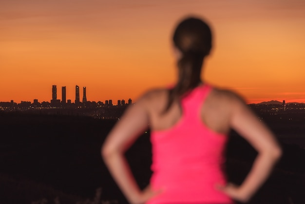 Woman on sport clothes watching sunset over city skyline. focus is on background.