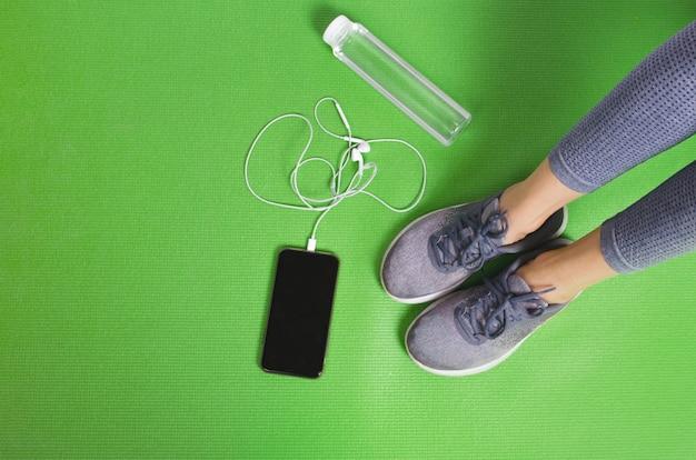 전화 및 음료 병 녹색 요가 매트에 여자 스포츠 다리