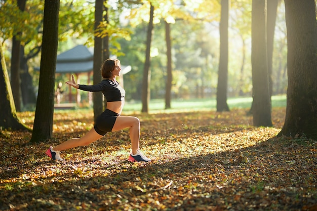 Woman in sport outfit warming up at park before jogging