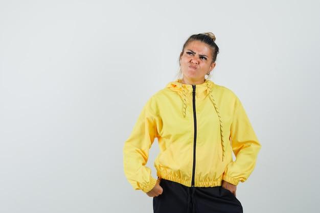 Donna in tuta sportiva in posa mentre pensa e sembra esitante, vista frontale.