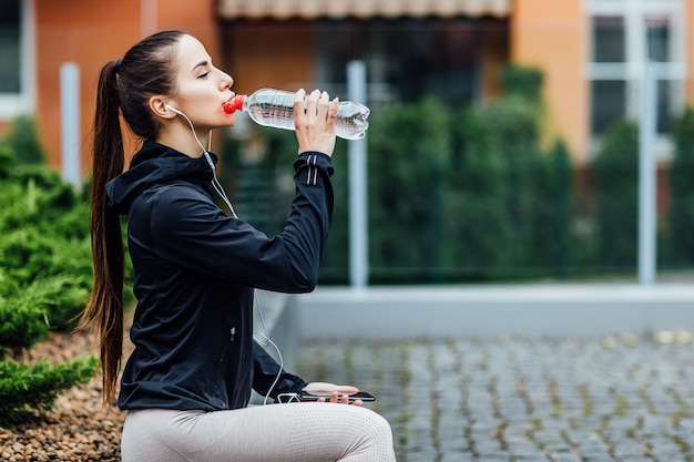 Woman in sport wear, drinking water on fresh air after morning running.