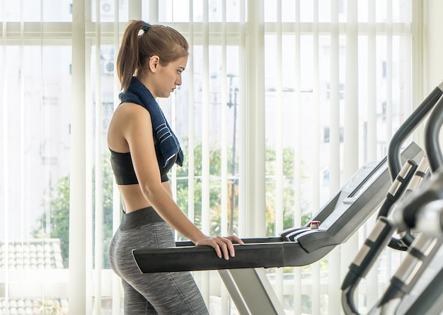 Woman in sport wear starting her run on a treadmill