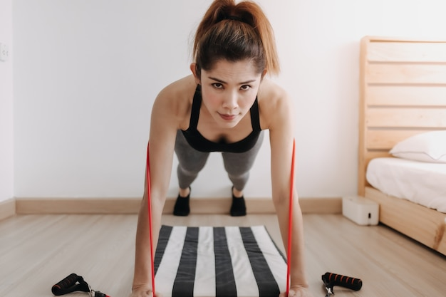 Woman in sport wears does resistance band push up workout in her room