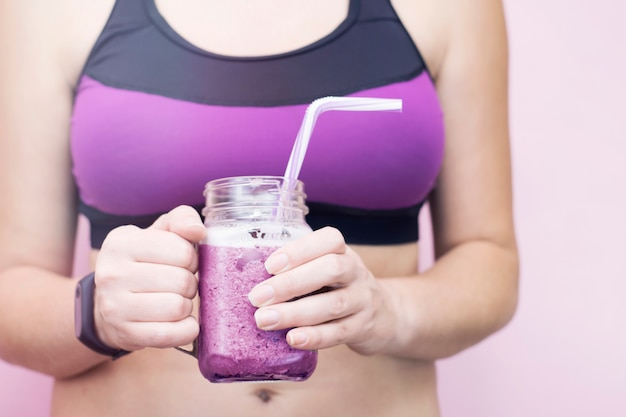Woman in sports clothes holding fruit blueberries detox smoothie after fitness workout