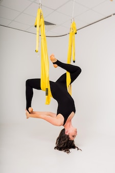 A woman in a sports jumpsuit does air yoga exercises