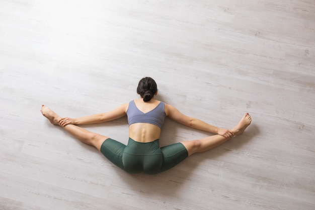 A woman in sports leggings and a short t-shirt, a yoga practitioner, performs a samokanasana exercise, sitting on the floor, a transverse split with the body tilted forward