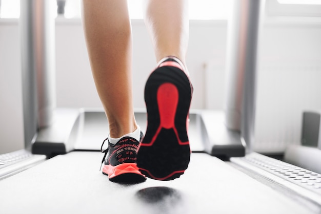 Woman in sports shoes running on treadmill