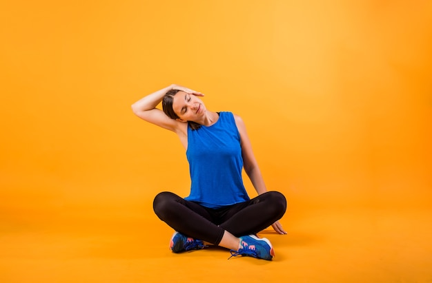 A woman in a sports uniform does a neck stretch on an orange wall
