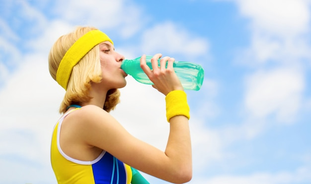 Woman in sports wear is holding a bottle of water. sports girl drinks water from a bottle on a sky background. healthy lifestyle concept. drinking during sport.