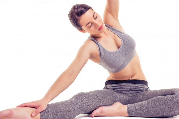 Woman in sports wear is stretching while doing yoga.