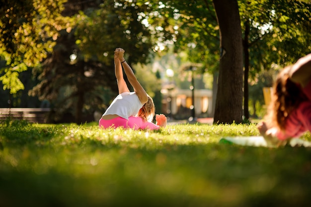 Woman in sportsuit practicing yoga poses in the park
