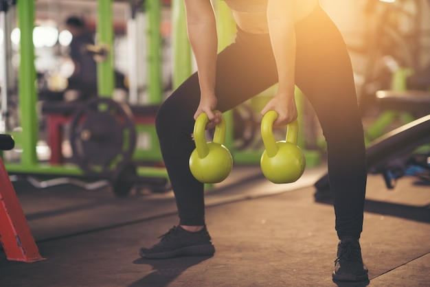 Woman in sportswear doing crossfit workout with kettle bell. healthy concept