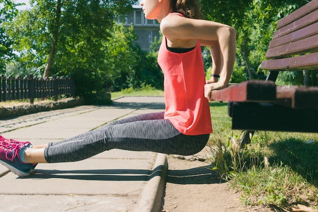Woman in sportswear doing exercise on triceps on park bench