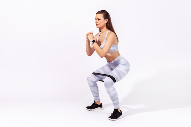 Woman in sportswear doing squats with resistance band on knees, pumping legs and glutes muscles
