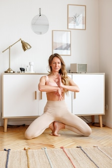 Woman in sportswear doing yoga at home