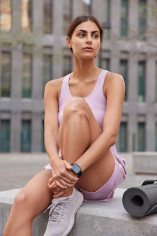 Woman in sportswear focused aside takes break after cardio training has workout outdoors poses near fitness mat wears trainers looks pensively into distance