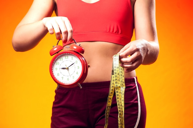Woman in sportswear holding alarm clock and meter. fintess time and dieting concept
