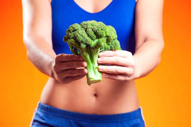 Woman in sportswear holding broccoli. people, fitness and dieting concept